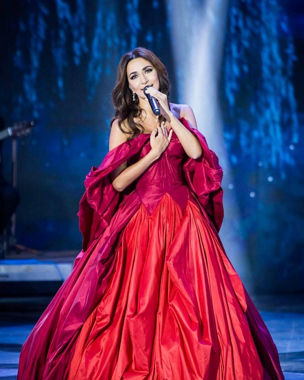 Зара исполняет песню на концерте в фото